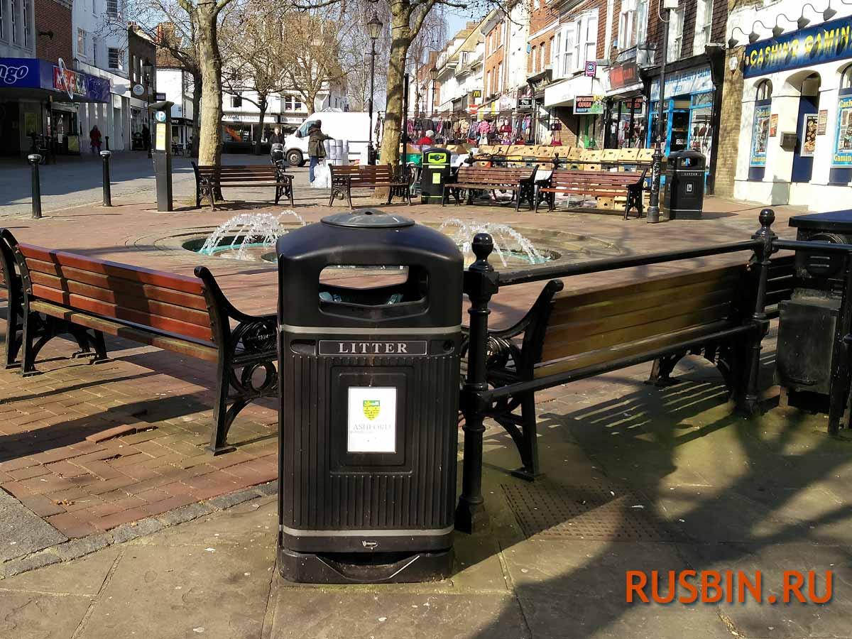Урна для мусора Glasdon Jubille черная с пепельницей установлена на площади в городе