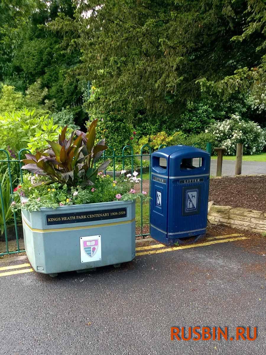 Синяя уличная мусорная урна Glasdon Jubille в красивом парке